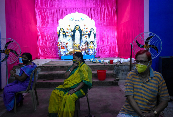 """People are wearing protective mask and sitting inside a """"pandal"""" or a temporary platform on the occasion of Durga Puja festival, amidst the spread of the coronavirus disease (COVID-19), in Kolkata."""