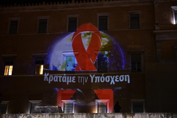 """Celebration of World AIDS Day on December 1, 2020 with the theme """"Global Solidarity, Common Responsibility"""" in the building of the Hellenic Parliament with the message """" We keep the Promise""""."""