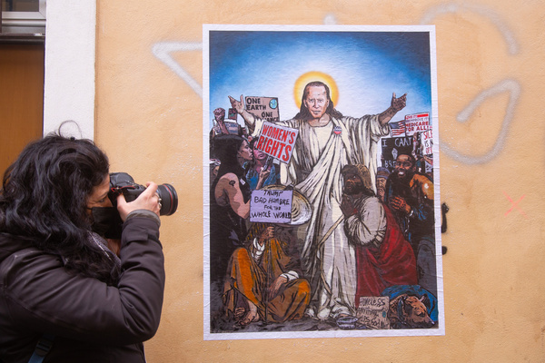 """A woman taking a picture of a mural titled """"The Savior?"""" made by Harry Greb in Vicolo Santa Rufina in the Trastevere district of Rome, where the new President of the United States of America Joe Biden is identified as the Savior, as the hope for the United States for social redemption, for a more right, with the battles that Biden became the bearer during the election campaign."""