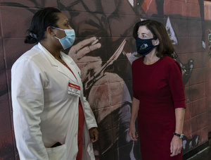 Lieutenant Governor Kathy Hochul (red dress wearing face mask)  speaks with Dr. Yomaris Pena of SOMOS Community Care during her visit of state vaccination site for COVID-19 at Aqueduct Race Track - Racing Hall. Lieutenant Governor Kathy Hochul tours State vaccination site and thanks healthcare workers. New York City Mayor Bill de Blasio said Tuesday, January 19, that the city will run out of first doses of COVID-19 vaccine sometime Thursday, January 21 without fresh supplies, city run sites started to reschedule appointments for the vaccination to the next week.