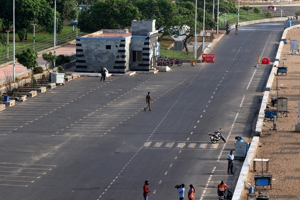 A police personal crosses the service road of Marina beach after a lockdown was imposed as a preventive measure against the spread of the Covid-19 coronavirus, in Chennai.