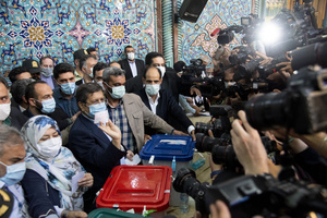 Presidential election candidate Abdolnasser Hemmati, former Central Bank chief, shows his ballot paper while voting at a polling station Tehran, Iran, Friday, June 18, 2021.