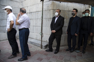 Rostam Qasemi (C) queue for voting in the presidential election at a polling station in Tehran, Iran, Friday, June 18, 2021.