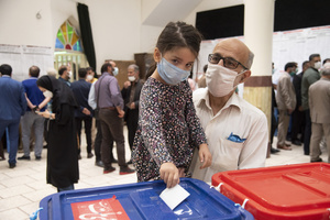 The granddaughter of a voter casts his ballot for the presidential election at a polling station in Tehran, Iran, Friday, June 18, 2021.