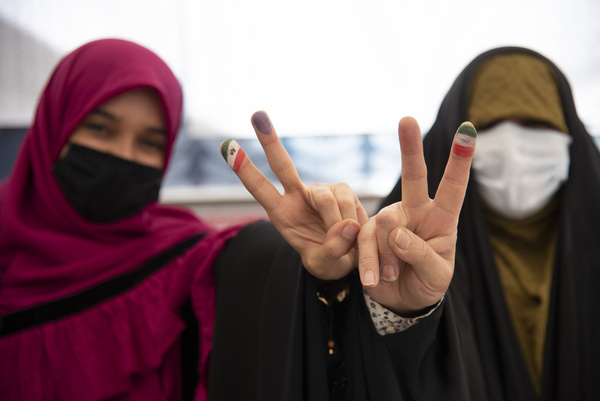 Two women flash the victory sign after voting at a polling station Tehran, Iran, Friday, June 18, 2021.