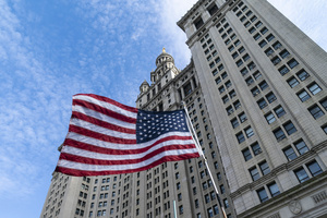 American flag seen in front of Municipal David Dinkins Building during municipal workers of the city march across Brooklyn bridge and rally at City Hall Park against vaccination mandate. Municipal workers from New York Police Department, Sanitation Department, Fire Department, Department of Education, Department of Correction, Parks Department, City Health and Hospitals, Metropolitan Transit Authority and other city office workers mandated by mayor to get vaccinated against COVID-19 disease by November 1, 2021 or will be left out of work and out of paycheck. More than 5 thousand protesters participated and they were joined by Republican Party mayoral candidate Curtis Sliwa.