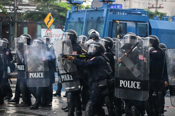 Riot police block road to 1st Infantry Regiment by containers and crackdown the protesters who are demanding vaccine against COVID-19.