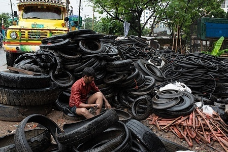 Workers are loading truck with old used tyres on a rainy day in Dhaka. The spare tyres are used to process as fuel for a brick kiln.