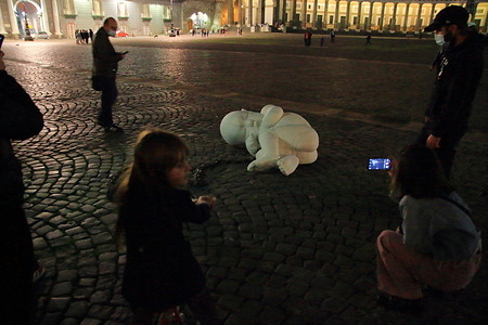 """The work of the Neapolitan artist Jago suddenly appeared in Piazza del Plebiscito. It represents a fetus of a child curled and with umbilical cord represented by a chain. The work is entirely made of marble with the title """"Look-down"""", that is look down. He wants to invite in this phase of the pandemic not to forget the poorest and the people most affected by this pandemic and the economic crisis."""