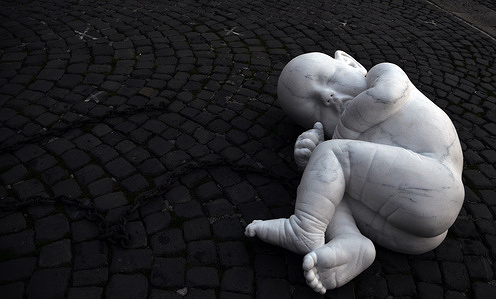 """The art in the Covid-19 era """"Look Down"""", the marble statue positioned in Plebiscito Square, the opera of Italian artist, Jacopo Cardillo known as Jago. Social crisis, pandemic and vulnerability, represented with marble statue were child is tied up by chain. This work represent the iconic emblem of the life during this pandemic."""