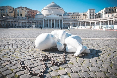"""A large stone infant sculpture by Jacopo Cardillo known as Jago, shows a child curled up and in suffering. Naked, lying on the floor of the Piazza del Plebiscito square, he will remain there until the beginning of January. As if to symbolize the most fragile humanity under the ax of the virus. Renamed """"Look-down"""". Look down, look at the least, it is the frail who have even less voice than yesterday."""