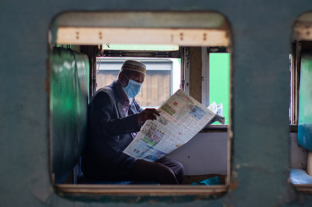 An old man reads a newspaper while wearing a face mask and maintaining social distance in a train amid the COVID-19 crisis. Bangladesh's Covid-19 tally of cases climbed up to 4.71 lakh with 2,336 new infections being reported in a day. 388,379 people have recovered so far pushing the national recovery rate to 82.3 per cent.