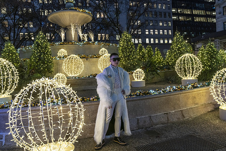 Influencer and fashion blogger Tim Shang wearing jacket by Opening Ceremony, coat by Pyer Moss, brooch by Versace poses at Christmas decorations on Pulitzer Fountain.