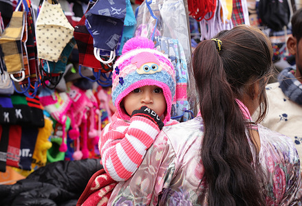 A child covered with warm cloth at a market during a cold morning in Beawar.