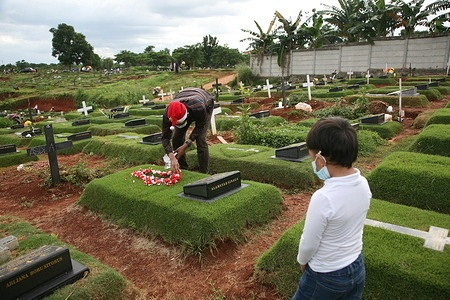 At the Christmas 2020 celebration, a number of residents paid a pilgrimage to the graves of relatives at the special graves of Covid-19 victims at the Pondok Ranggon Public Cemetery, Jakarta, Friday (25/12/2020). This year's Christmas moment was used by a number of Christians to make pilgrimages and pray for relatives who were buried under the Covid-19 protocol.