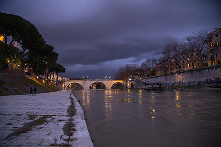 View of the Tiber partially covered the quay that surrounds the Tiber Island due to the heavy rains that are falling in Rome. Some curious people walk on the quay and take pictures.