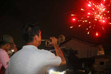 A man blows a trumpet during the New Year Countdown in Antipolo City.