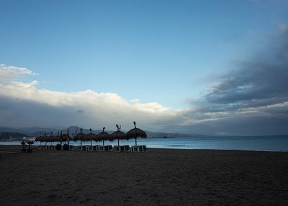 Clear and stormy skies are seen from an empty beach.