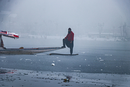 SRINAGAR, INDIA, 14 JANUARY 2021 - A Kashmiri boatman stands on the frozen Dal lake after Srinagar recorded lowest temperature at minus 8.4 degrees Celsius on January 14, 2021. In 1991, Srinagar had recorded low of minus 11.8°C while the lowest ever was endured on 31 January 1893. Due to the unprecedented dip in night temperatures in the valley lately, Dal Lake and other water bodies here have frozen.