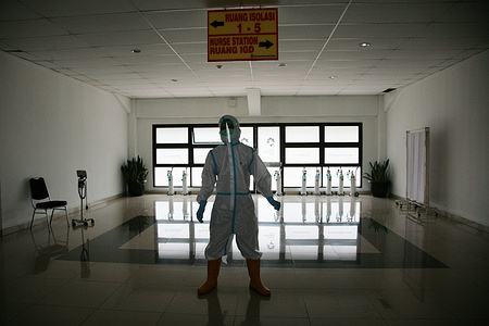 Health workers in Hazmat suits at the Emergency Hospital as well as an isolation room for People without Covid-19 Symptoms at the Patriot Candrabhaga Stadium, Bekasi, West Java. Patriot Candrabhaga Stadium, Bekasi City, has become an emergency hospital as well as an isolation room for people without symptoms of Covid-19. The Bekasi City Government has prepared a treatment area and isolation room for patients without symptoms of Covid-19 in this stadium, to accommodate residents who cannot carry out independent isolation at home.
