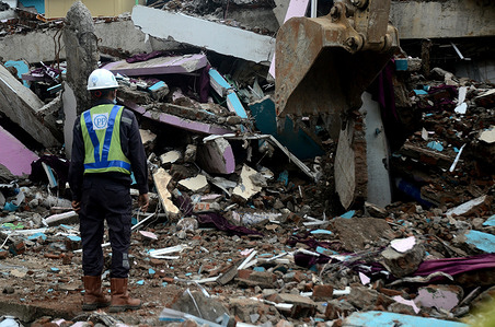 Worker use excavators to clean debris from the 6.2 magnitude earthquake to search for victims in Mamuju, West Sulawesi. Until now, the 6.2 magnitude earthquake has killed at least 73 people.
