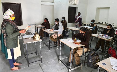 A teacher wearing face mask takes the class of students with proper social distancing at a government school that was reopened after closure for 309 days due to COVID-19 pandemic in Beawar.