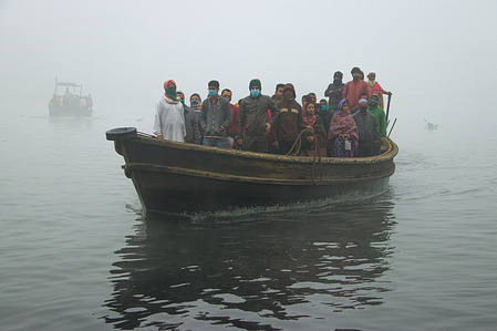 Passengers cross over Shitalakshya River by boats without social distancing on a densely foggy morning amid the COVID-19 crisis. Bangladesh's Covid-19 tally of cases climbed up to 531,799 with no new infections being reported in a day. 476,413 people have recovered so far pushing the national recovery rate to 89.6 per cent.
