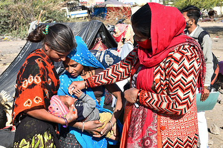 An Anganwadi health worker administers polio vaccine drops to a child at a slum area during Pulse Polio eradication program in Beawar.
