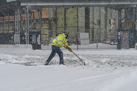 Maintenance worker clear from snow entrance to construction site atHudson Yards covered with snow as major storm impact New York City with more than a foot expected on the ground. This snow storm called nor'easter storm. Heavy snowfall expected to continue for more than 24 hours. Snow storm impacted all North East of the US.