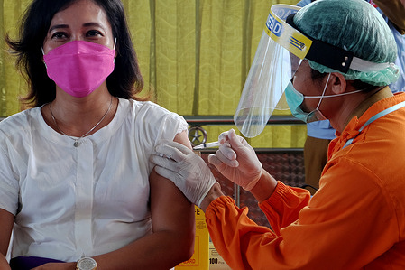 Medical personnel injects the Covid-19 Sinovac vaccine into another medical personnel.
