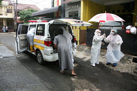 A number of health workers evacuate a resident suspected of having the Covid-19 virus at Jatiwaringin Asri Housing, Bekasi, Indonesia, to be taken to a special referral hospital for Covid-19 patients, Tuesday (02/02/2021). The Covid-19 case in Indonesia has not shown signs of decreasing. In fact, in recent times the cases have even jumped sharply.