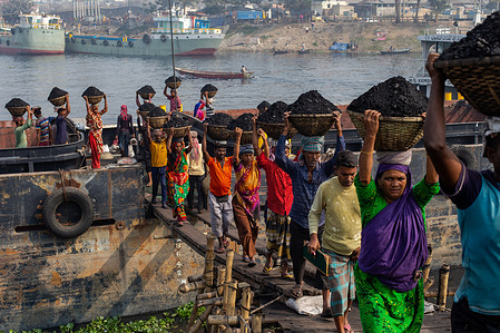 Coal workers in the coal industry unload a boat on the Buriganga River in Gabtoli. Average workers earn around 1 USD per day for their hard work.