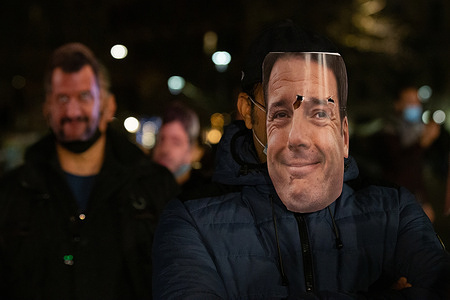 Man wears a mask with the face of Matteo Renzi
