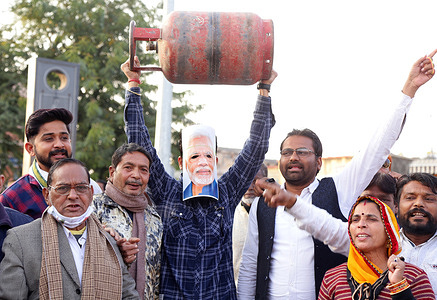 Congress party activists wearing facemask of Indian Prime Minister Narendra Modi demonstrate with a gas cylinder during a protest against hike in fuel prices, in Beawar. Petrol, diesel prices hiked by 30 paise for second consecutive day in India. Price of domestic gas cylinder has increased by Rupees 25.