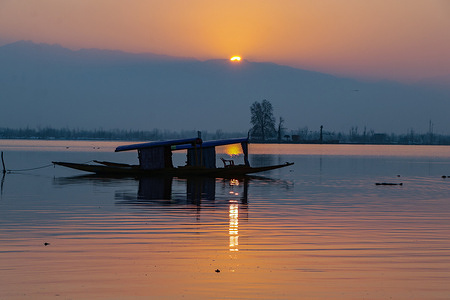 SRINAGAR, INDIA, 6 FEBRUARY 2021 - In the middle of Dal Lake Shikara sailing with a beautiful winter sunset on Saturday, February 26, 2021. Kashmir valley recently witnessed the harshest Chilai Kalan in the last 30 years during which low temperatures caused freezing of water bodies including Dal Lake.