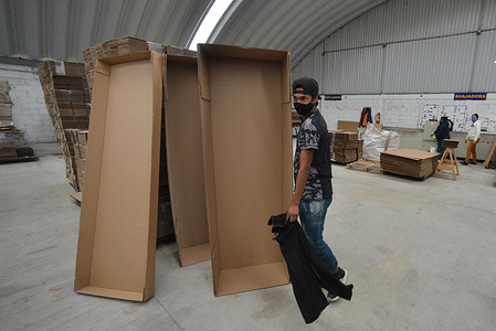 A  worker of KJ cardboard box factory, during the the assembly of an coffin  made of cardboard. Due the increase of deaths of covid and the increase  unemployment in the country, KJ cardboard factory implement caskets manufactured by recycled cardboard, to persons who are low income and do not have the support to buy a wooden or aluminum casket. These  cardboard coffin are primarily intended for  companies workers or funeral homes.