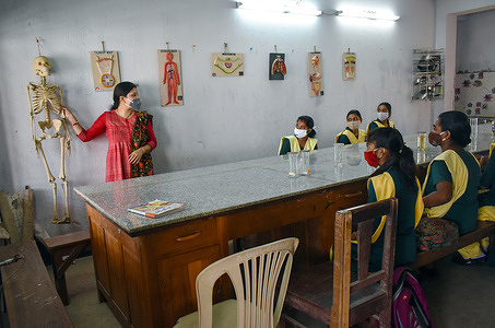 Schools students attend a class at a Government school as the schools reopened after almost 11 months of break due to the Covid-19 coronavirus pandemic in Kolkata.
