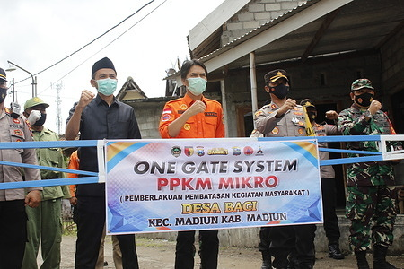 Madiun Regent Ahmad Dawami (in orange) with members of the Regional Leadership Coordination Forum (Forkopimda) when inaugurating a micro-scale Community Activity Restriction (PPKM) post at the Bagi Village office, Madiun District and Jerukgulung Village, Balerejo District, Madiun Regency. Micro PPKM has been implemented in 4766 neighborhoods (RT) in Madiun Regency and all have preparedness in order to prevent and handle Covid-19. Micro PPKM is the government's effort to overcome and stop the spread of Covid-19, especially in Madiun Regency. Everyone hopes that the establishment of this micro PPKM post can increase public awareness in implementing health protocols