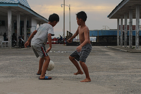 Activities of children playing footballs in the late afternoon in the parking lot of the Lais River pier in Palembang, South Sumatra on February 14, 2021.