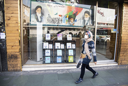 Portraits of supreme leader of Iran, Ayatollah Ali Khamenei and the Iran`s late leader Ayatollah Khomeini are reflected in a bookstore window in Enghelab(Revolution) street, Tehran, Iran. Since the beginning of February 2021, the number of people infected with the Coronavirus has been increasing in Iran.