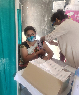 A medic administers the first dose of Covishield vaccine on a teacher during the countrywide inoculation drive, at a government school in Bundi.