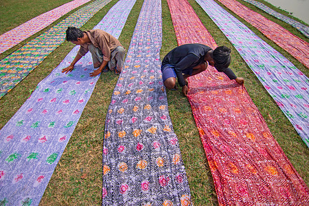 Workers are drying Batik cloth under the sun in an open field as part of the process of creating traditional Batik. In this techniques wax is used to create stunning patterns on a huge scale. The wax prevents the dye from penetrating the area it is placed on, allowing workers to create amazingly complex multi-colored designs. Then, they  soak the cloths in a dying emulsion before rolling the large cotton, silk, or wool cloth in the hot sun to dry.
