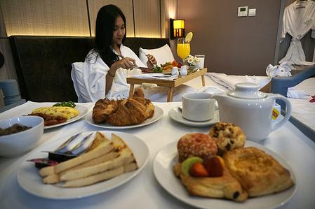 A woman having room service American Breakfast at El Royale Hotel Yogyakarta.