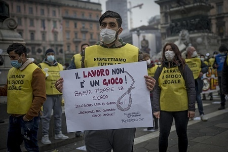 """A protester holding a banner during """"Reopen legal game, we want to work"""" protest in the square to ask for the reopening of activities related to gambling in the yellow zone. The protest of the workers of the sector who want to return to work in the regions that fall within the yellow zone was held in Piazza Duomo in Milan."""