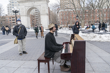 Street Musician Andrew Kalleen plays piano in cold weather on Washington Square Park