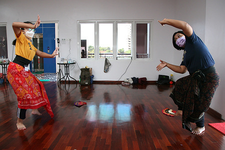 By wearing a mask and implementing health protocols, a female dance coach and a girl in a traditional dance class practice Balinese traditional dances at a dance studio in the Tebet area, South Jakarta, Sunday (21/2/2021).