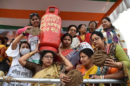 Activist of the All India Trinamool Congress (TMC) Mahila Morcha (Women Wing) hold a dummy cooking gas cylinder and Ghutes or cow dung cakes to protest against rising fuel prices across country at the sit-in demonstration.