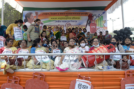 All India Trinamool Congress or AITMC women activists hold model of a gas cylinder during a sit in demonstration to protest against fuel price hike.