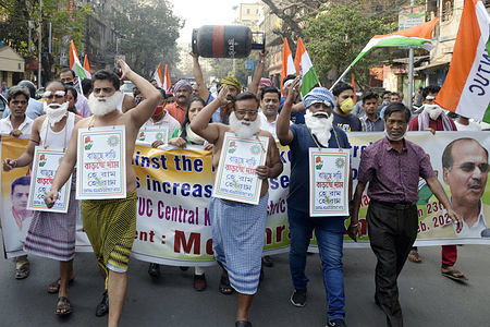 Congress activists wear towels and shout slogan during a rally to protest against fuel price hike.