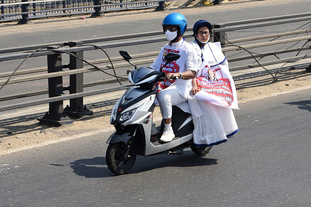 West Bengal Chief Minister Mamata Banerjee rides pillion on an electric scooter to reach State Secretariat Nabanna to protest against fuel price hike.